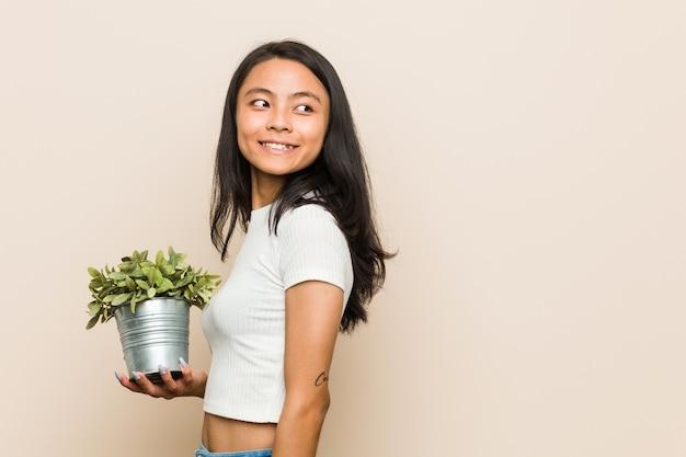 Młoda azjatycka kobieta trzymająca roślinę wygląda na bok uśmiechnięta, wesoła i przyjemna.