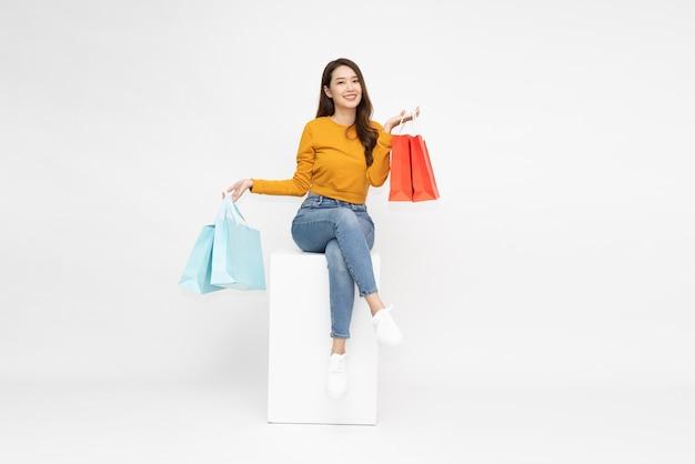 Młoda azjatycka kobieta trzymająca torby na zakupy i siedząca na białym pudełku na białym tle