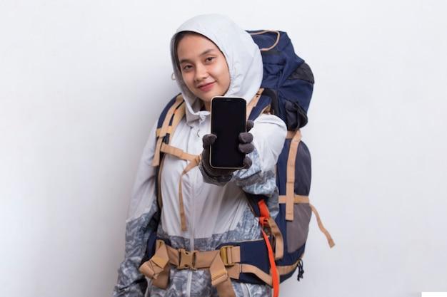 Młoda azjatycka kobieta turysta pokazująca telefon komórkowy na białym tle