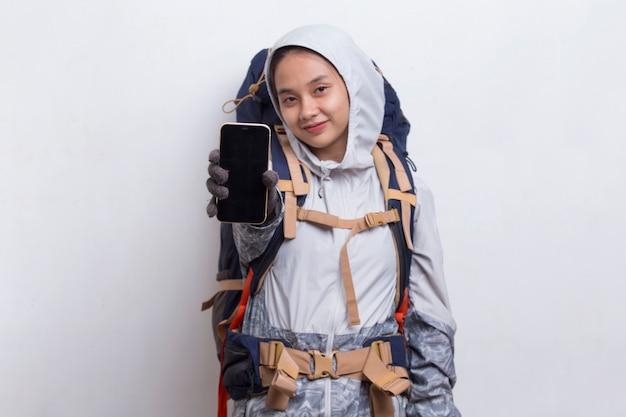 Młoda Azjatycka Kobieta Turysta Pokazująca Telefon Komórkowy Na Białym Tle Premium Zdjęcia