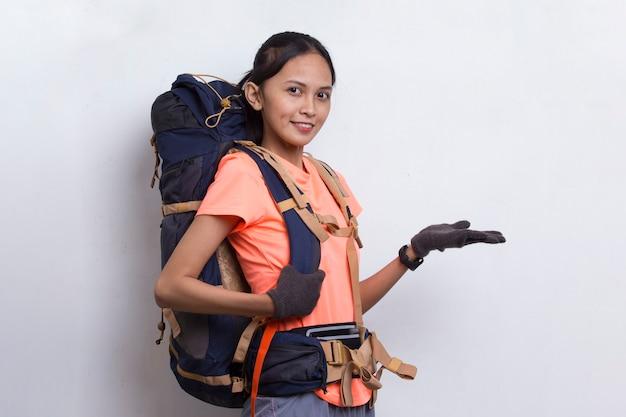 Młoda azjatycka kobieta turysta z plecakiem wskazującym palcem na pustej przestrzeni na białym tle