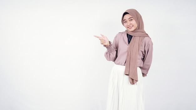 Młoda azjatycka kobieta ubrana w hidżab wskazujący puste miejsce po prawej stronie na białym tle