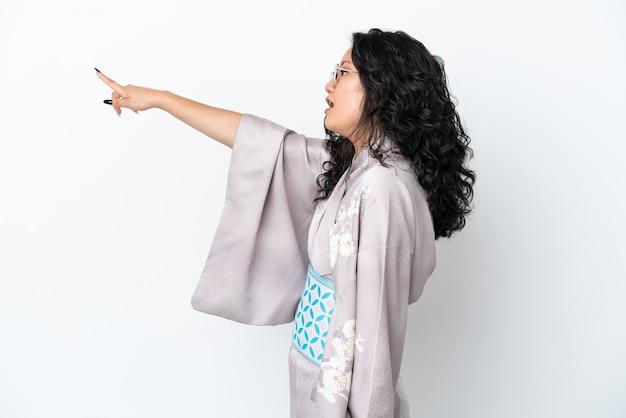 Młoda azjatycka kobieta ubrana w kimono na białym tle wskazującym od tyłu