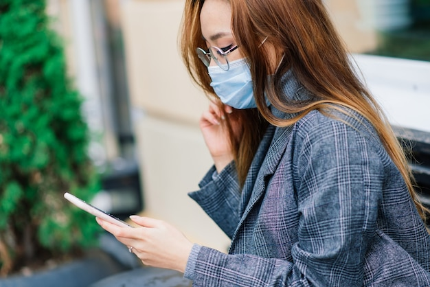 Młoda azjatycka kobieta ubrana w maskę stoi na krajowej ulicy. nowa normalna epidemia covid-19