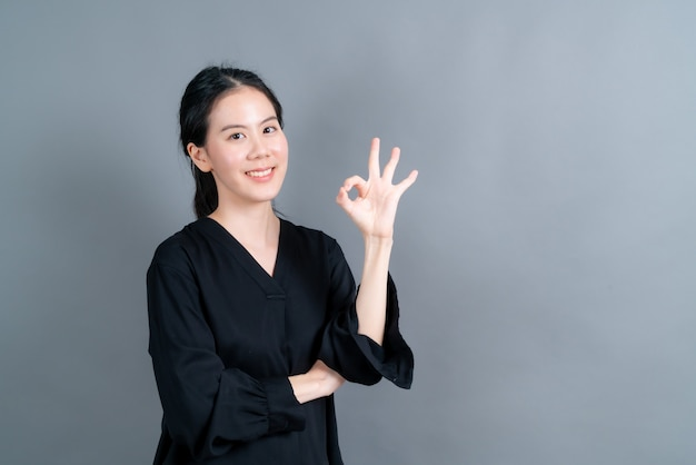 Młoda azjatycka kobieta uśmiecha się i pokazuje znak ok na szarej ścianie