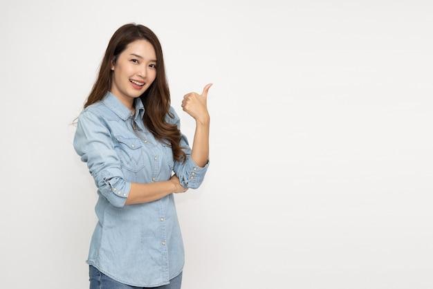 Młoda azjatycka kobieta uśmiecha się i wskazuje palcem na puste miejsce na kopię na białym tle