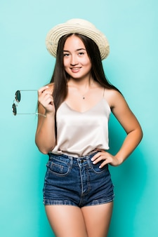 Młoda azjatycka kobieta uśmiecha się turkusowego tło w kapeluszu i okularach przeciwsłonecznych
