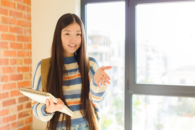 Młoda azjatycka kobieta uśmiecha się, wita i oferuje uścisk dłoni, aby zamknąć udaną transakcję, koncepcja współpracy