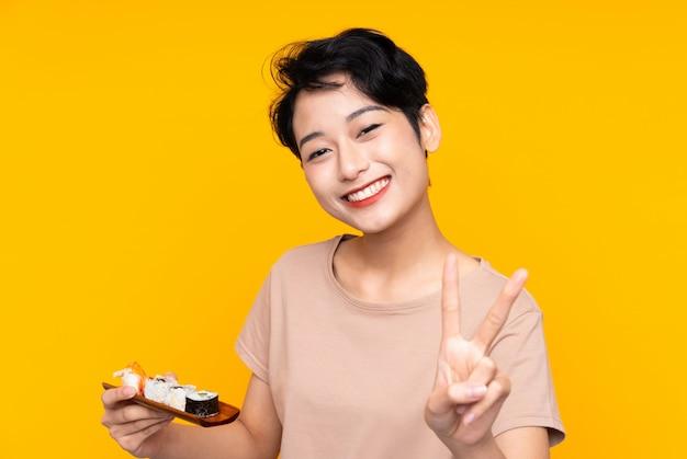 Młoda azjatycka kobieta uśmiecha się zwycięstwo znaka i pokazuje z suszi