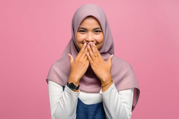 Młoda azjatycka kobieta uśmiechając się i obejmując usta ręką