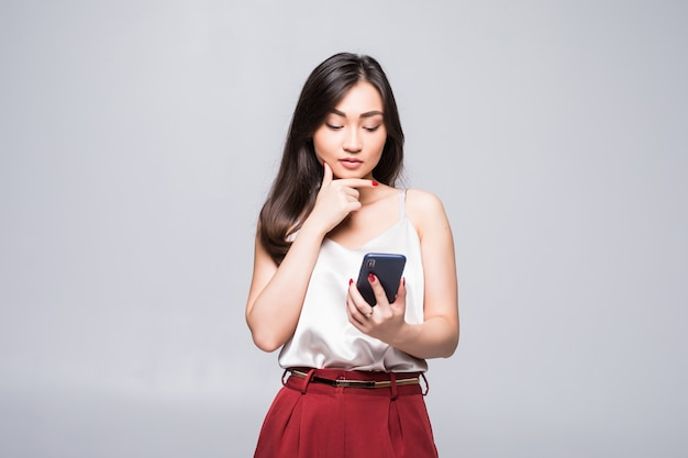 Młoda azjatycka kobieta używa mądrze telefon odizolowywającego na biel ścianie.