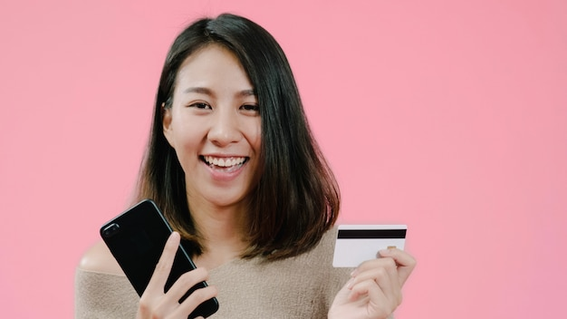 Młoda azjatycka kobieta używa smartphone kupuje online zakupy kredytowej karty czuć szczęśliwy ono uśmiecha się w przypadkowej odzieży nad różowym tła studia strzałem.