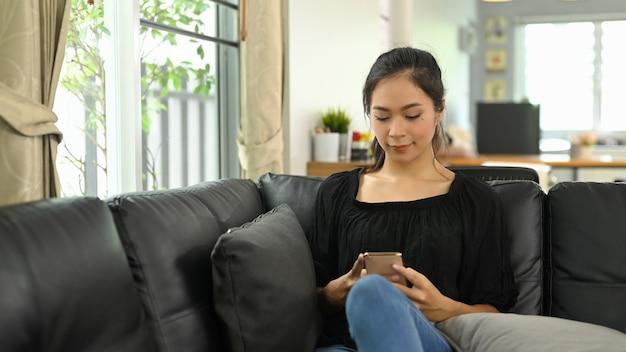 Młoda azjatycka kobieta używa telefonu komórkowego, leżąc na czarnej skórzanej kanapie