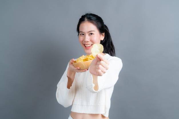 Młoda azjatycka kobieta w białym swetrze je chipsy ziemniaczane na szarym tle