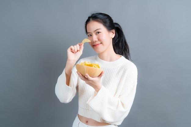 Młoda azjatycka kobieta w białym swetrze je chipsy ziemniaczane