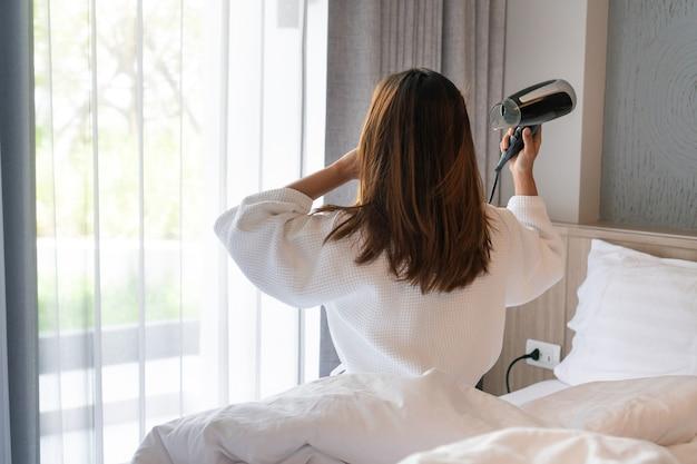 Młoda azjatycka kobieta w białym szlafroku siedzi na łóżku i ciosem, susząc włosy rano