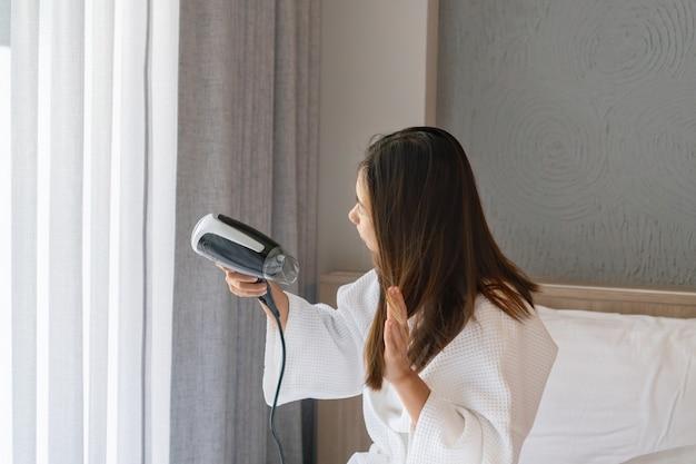Młoda azjatycka kobieta w białym szlafroku siedzi na łóżku w pokoju hotelowym i suszy włosy rano