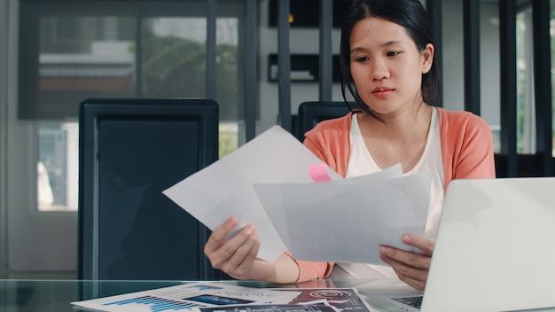 Młoda azjatycka kobieta w ciąży rejestruje dochody i wydatki w domu. mama dziewczyna szczęśliwa za pomocą laptopa rekord budżetu, podatków, dokumentów finansowych, e handlu pracy w salonie w domu.