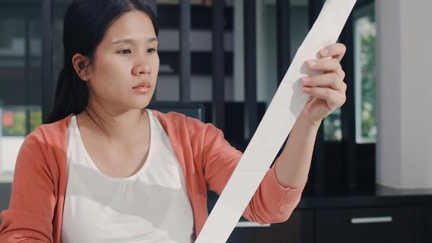 Młoda azjatycka kobieta w ciąży rejestruje dochody i wydatki w domu. mama zmartwiona, poważna, stresująca podczas rekordowego budżetu, podatków, dokumentów finansowych pracujących w salonie w domu.