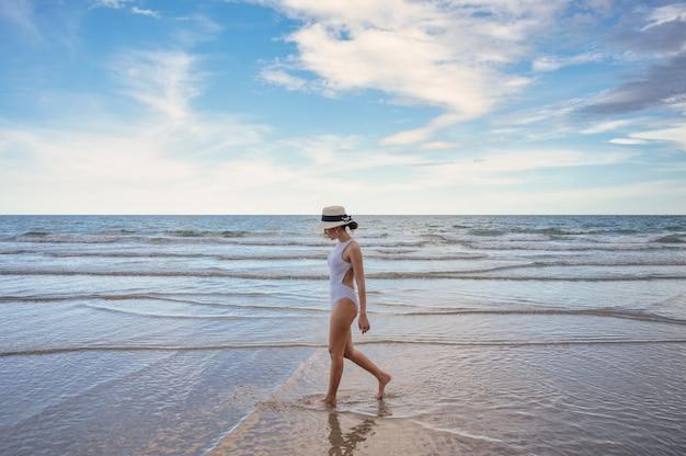 Młoda azjatycka kobieta w kapeluszu w strojach kąpielowych, spacer na plaży z błękitnym niebem w tropikalnym morzu. koncepcja lato i wakacje
