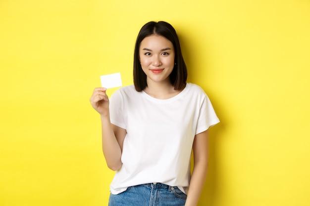 Młoda azjatycka kobieta w przypadkowej białej koszulce pokazuje plastikową kartę kredytową i uśmiecha się do kamery, żółta.
