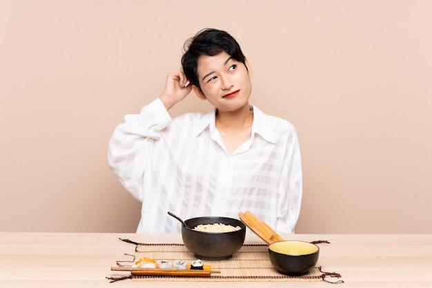 Młoda azjatycka kobieta w stole z pucharem kluski i suszi ma wątpliwości i z zmieszanym wyrazem twarzy