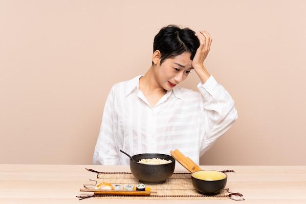 Młoda azjatycka kobieta w stole z pucharem kluski i suszi ma wątpliwości z zmieszanym wyrazem twarzy