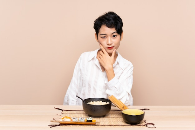 Młoda azjatycka kobieta w stole z pucharem kluski i suszi myśleć pomysł