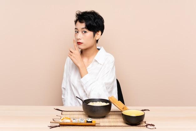 Młoda azjatycka kobieta w stole z pucharem kluski i suszi robi cisza gestowi