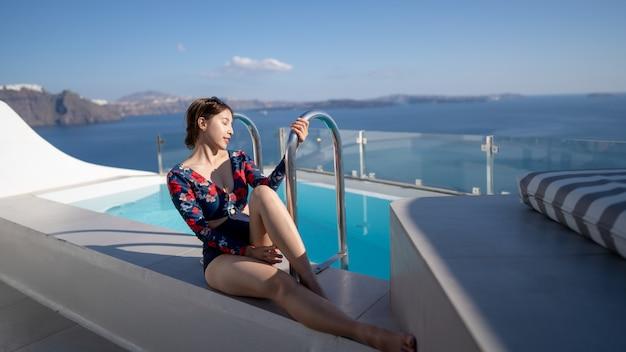Młoda azjatycka kobieta w swimsuit siedzi blisko ligustrowego basenu cieszy się widoku oia wioskę w santorini wyspie, grecja.
