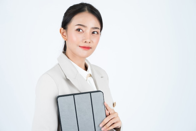 Młoda azjatycka kobieta w szarym kolorze, jest mądra i pewna siebie. kierownik myśli o pracy.