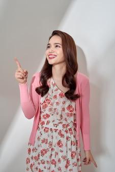 Młoda azjatycka kobieta wskazując palcem i patrząc w tym samym kierunku. zdjęcie do projektów biznesowych, prezentacji produktów, tematów interpersonalnych (randki, flirty). obraz z miejscem na kopię na białym tle