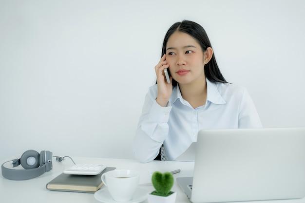 Młoda azjatycka kobieta wykonuje rozmowę telefoniczną, analizując wykresy, aby ustalić nowy cel biznesowy