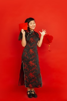 Młoda azjatycka kobieta z czerwoną kopertą i chińską latarnią na białym tle na czerwonej ścianie