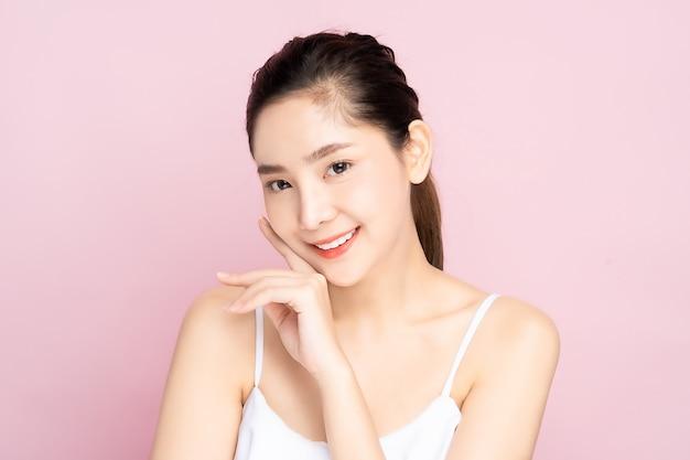 Młoda azjatycka kobieta z czystą świeżą białą skórą delikatnie dotykającą własnej twarzy w pozie piękna