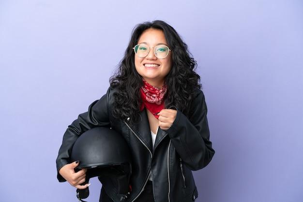 Młoda azjatycka kobieta z kaskiem motocyklowym na fioletowym tle świętująca zwycięstwo w pozycji zwycięzcy