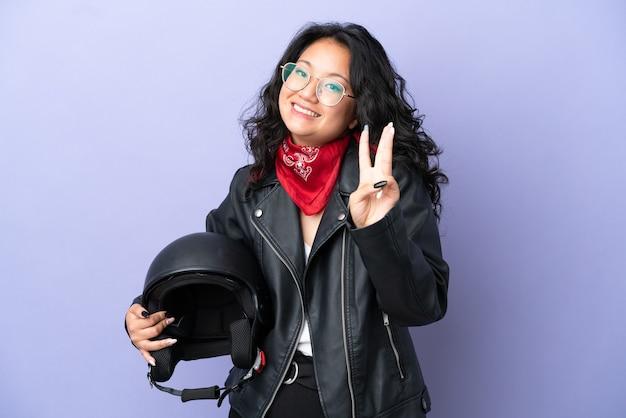 Młoda azjatycka kobieta z kaskiem motocyklowym na fioletowym tle szczęśliwa i licząca trzy palcami