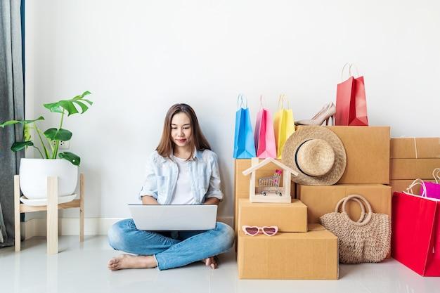 Młoda azjatycka kobieta z kolorową torbą na zakupy, modnymi przedmiotami i stosem kartonów w domu, koncepcja zakupów online na stronie internetowej z miejscem na kopię