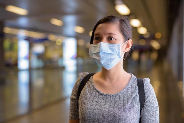 Młoda azjatycka kobieta z maską stojąc przy świetle na stacji metra