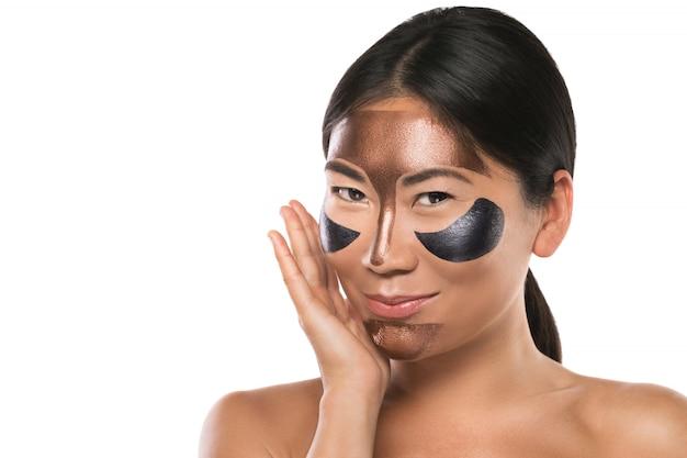 Młoda azjatycka kobieta z odkrywającą maską na jej twarzy