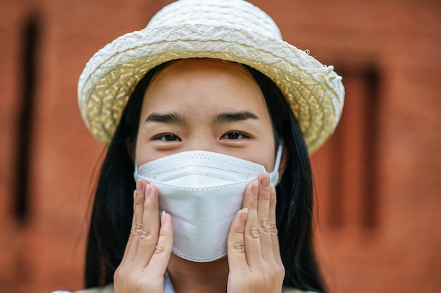 Młoda azjatycka kobieta z plecakiem nosząca kapelusz i maskę ochronną podczas podróży po zabytkowym miejscu