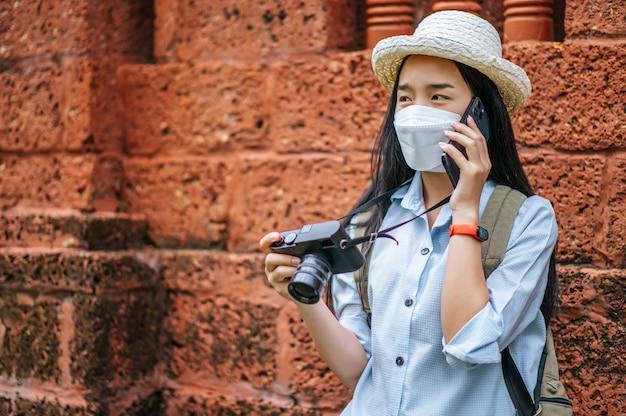 Młoda azjatycka kobieta z plecakiem w kapeluszu i masce ochronnej podczas podróży po zabytkowym miejscu, rozmawia ze smartfonem i trzyma aparat w ręku