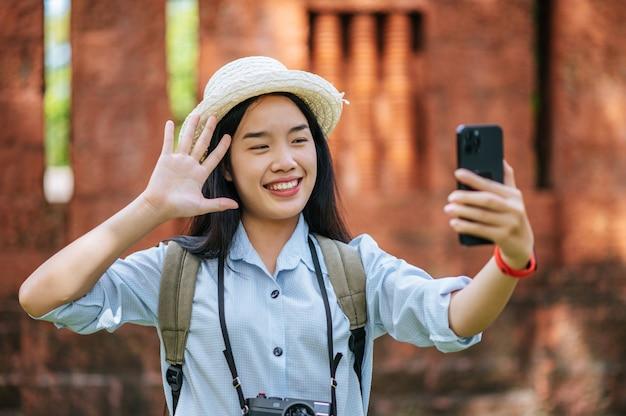 Młoda azjatycka kobieta z plecakiem w kapeluszu podróżująca po zabytkowym miejscu, używa smartfona i aparatu, robi zdjęcie z happy