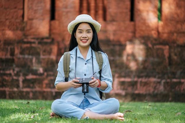 Młoda azjatycka kobieta z plecakiem w kapeluszu uśmiechnięta podczas podróży po zabytkowym miejscu, siedzi na trawie, aby się zrelaksować i użyć aparatu, zrobić zdjęcie z radością