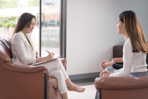 Młoda azjatycka kobieta z problemem zdrowia psychicznego spotyka się z psychologiem w celu konsultacji i terapii psychicznej. koncepcja psychologii i terapii psychicznej