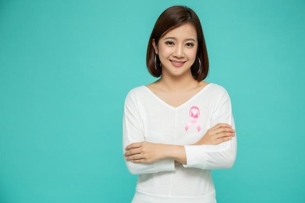 Młoda azjatycka kobieta z raka piersi różową tasiemką nad odosobnioną jasnozieloną ścianą