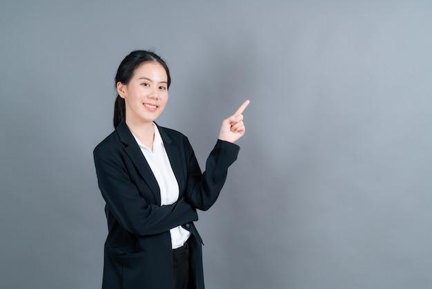Młoda azjatycka kobieta z ręką przedstawiającą na boku