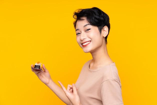 Młoda azjatycka kobieta z suszi i wskazywać je