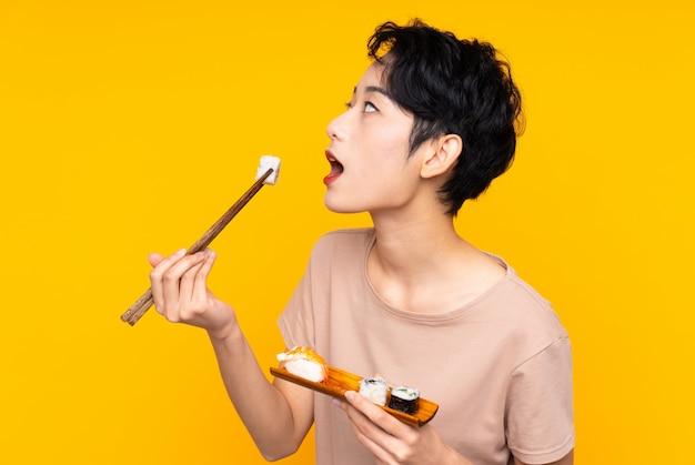 Młoda azjatycka kobieta z suszi nad kolor żółty ścianą