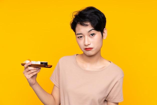 Młoda azjatycka kobieta z suszi z smutnym wyrażeniem